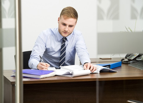 trainee financial adviser studying at his desk